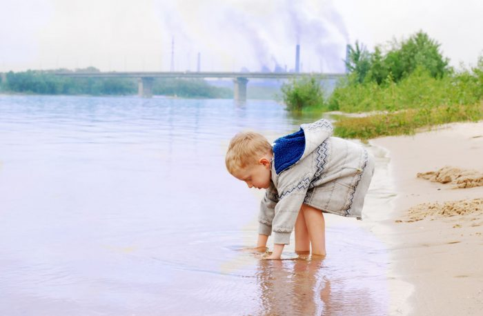 13858346 - playing little boy on the river coast near industrial plant