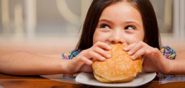 little girl eating hamburger