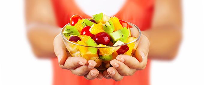 girl holding fruit bowl