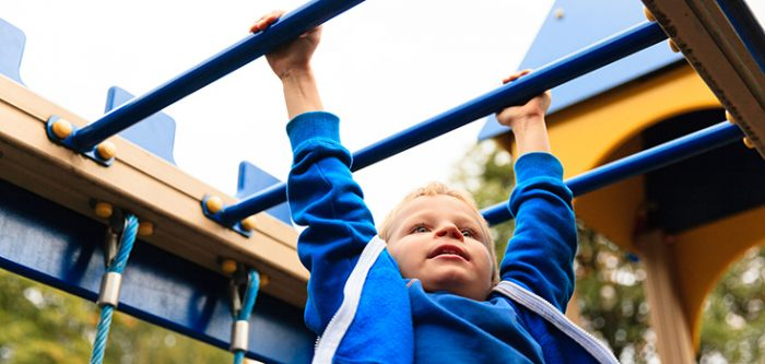 kid playing on monkey bars