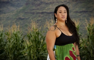 Malia Chun stands in front of the GE corn fields near her home. Source: MIKE COOTS FOR EARTHJUSTICE